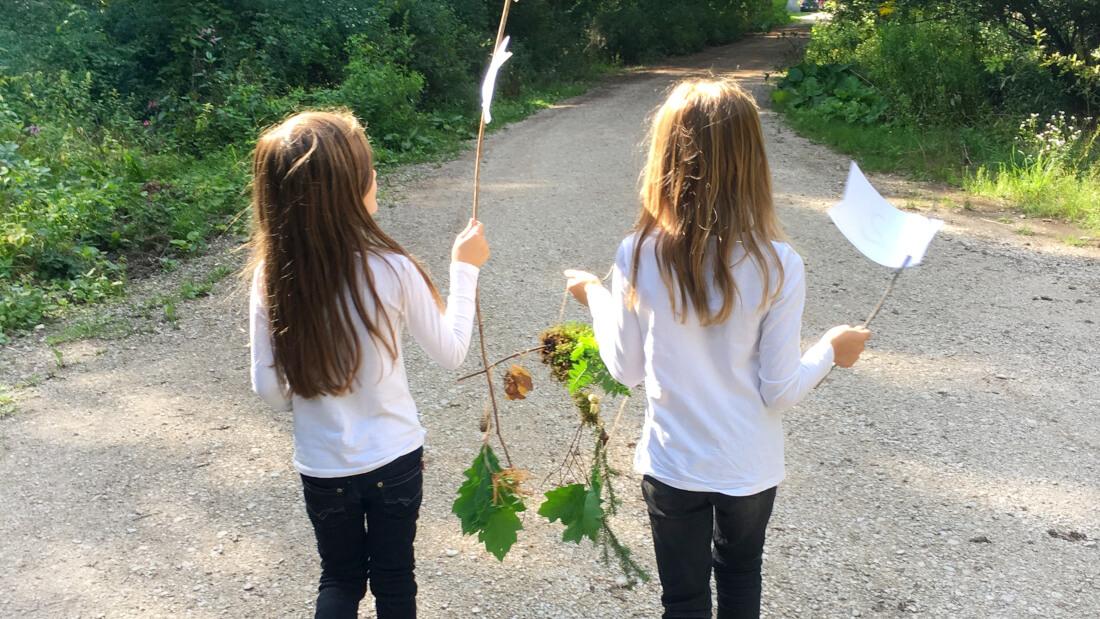 Bei einer anderen Aufgabe der Wald-Schatzsuche basteln die Kinder ein Mobile aus Blättern und Zweigen