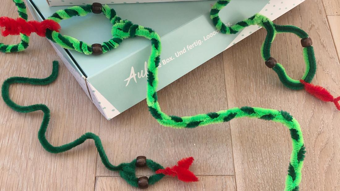 Die Pfeifenputzerschlangen kannst du aus verschiedenen Grüntönen basteln