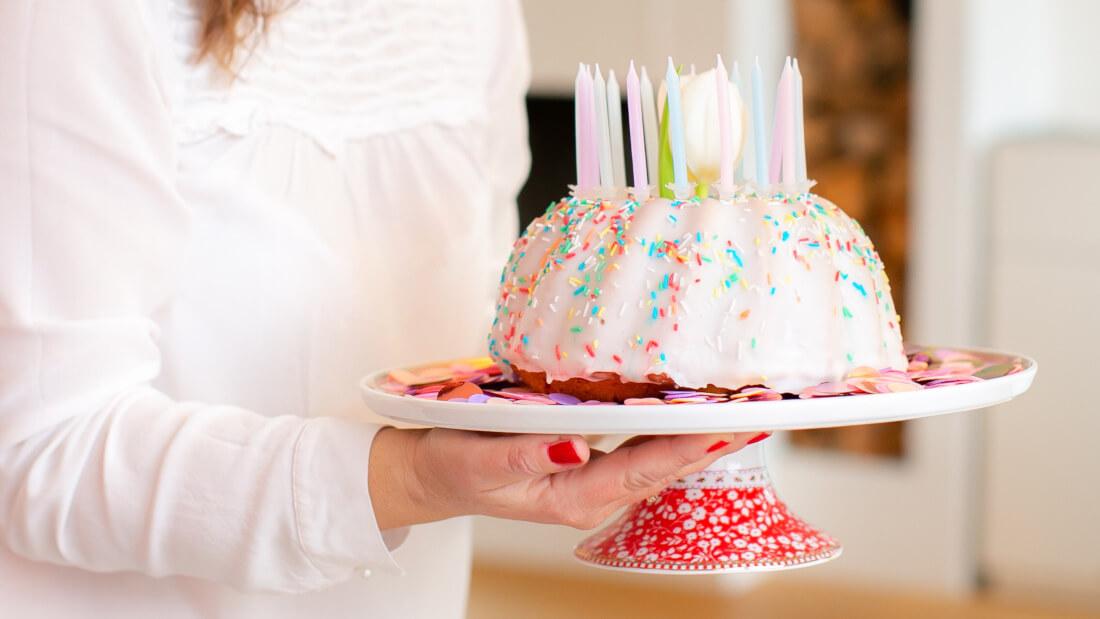 Ein einfacher Rührkuchen mit weißer Glasur und bunten Streuseln und Kerzen in Pastellfarben ist perfekt für eure Feen- und Einhornparty